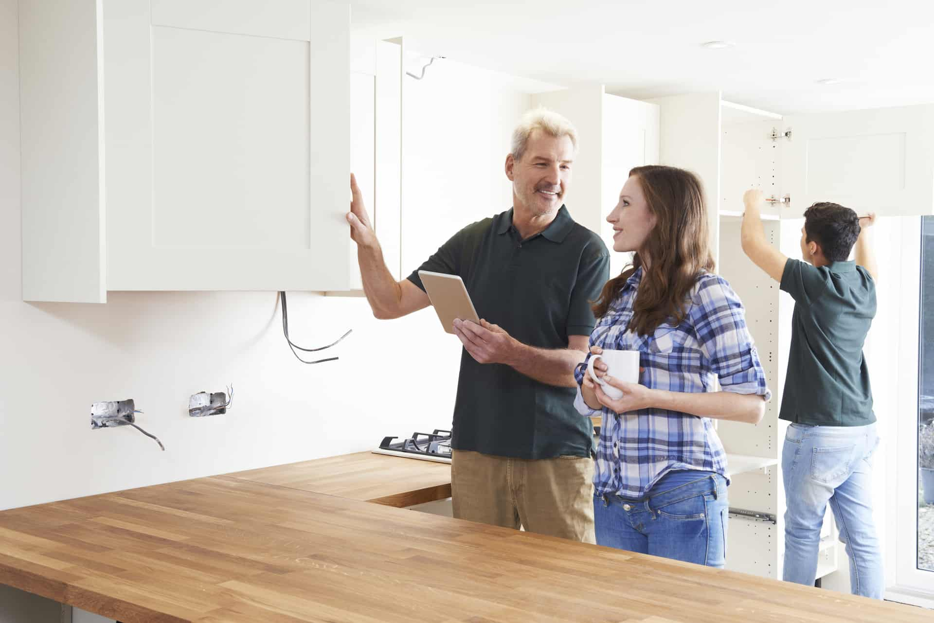 Woman With Carpenter Looking At Plans For Kitchen On Digital Tablet